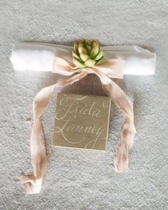 A calligraphed favor box and a napkin decorated with a hand-dyed silk ribbon and tiny succulent awaited guests at this wedding's place settings.