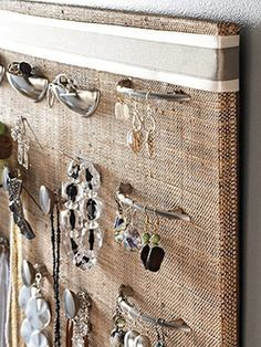 Knobs on a fabric covered cork board -- jewelry organization idea