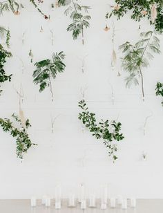 Greenery galore at this wedding floral wall, framed by candles. All white elements pop with these minimalistic accents.