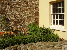 The bedroom window of Welcombe Coastal Barn overlooking the scree garden.  Since planted with climbing roses and a young Pear Tree trained as an espalier.