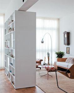 Note que a profundidade da estante é menor na face voltada para a cozinha (9 cm) do que na sala (32 cm). As prateleiras mais estreitas acomodam enfeites. O móvel ainda disfarça o pilar que restou da demolição de uma parede.