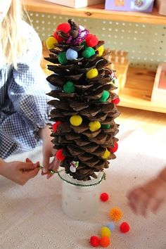 Decorate pinecone (as a stand-in for a Christmas tree) with pom poms and pipecleaners