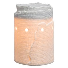 A raw-edged burlap texture enwraps a pristine porcelain warmer that glows with ethereal golden light.