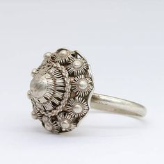 This beautiful silver ring is a traditional Dutch jewellery piece. Featuring what is called a Zeeuws knopje or Zeeuwse knoop, which is a part of the Dutch regional folkloric costume since the 18th century. The bigger the knot button, the richer and more honorable the wearer.  It is handmade out of silver. The filigree and beautiful symmetric shapes make it a really special piece.  Measurements: US size 9 1/2 19.5 mm/0.76 inch in diameter  The top part is 2 cm/0.78 inch wide  Ma...