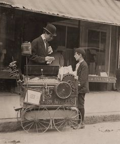 Little Salesmen: Joseph Severio, peanut vender, age 11 [seen with photographer Hine]. Been pushing a cart 2 years. Out after midnight on May 21, 1910. Ordinarily works 6 hours per day. Works of his own volition. All earnings go to his father. Wilmington, Delaware.