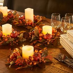 Multiple Fall Pumpkin Candle Rings filled with ivory-colored flameless candles create a beautiful Thanksgiving table decoration.
