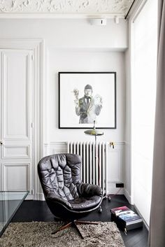 Living space with a vintage leather chair, a shag rug, and modern art
