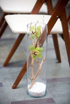 Glass vases filled with white rocks, sand blasted manzanita and green orchids made for a simple aisle treatment