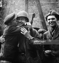 A Polish man embraces an Allied soldier, kissing his cheek, after being liberated from a Nazi forced labor camp in Germany during World War II.