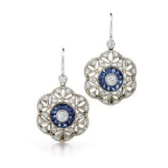 Juno sapphire and diamond earrings from the Kwiat Vintage Collection in 18K white gold  Evoking a floral motif, a ring of sapphires and bright diamonds accent a delicate drop earring.