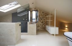 Beautifully restored stone house in Spain with classic mid-century furniture, large kitchen island, sleeping loft with deck & skylights by Dom Arquitectura.