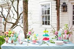 LOVE the branches in bloom in vases and lying on the table, the pots of flowers and the soft pastel treats - and the 3 different colored treats on the 3 tiered stand - one for each tray - love that