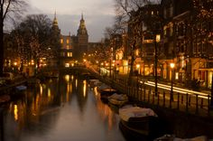 The trees are wrapped in festive fairy lights along the canal in Amsterdam.