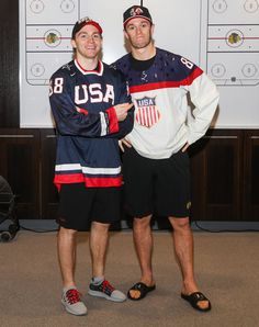 Patrick Kane and Jonathan Toews take a photo in the locker room sporting USA jerseys after making a bet with each other.