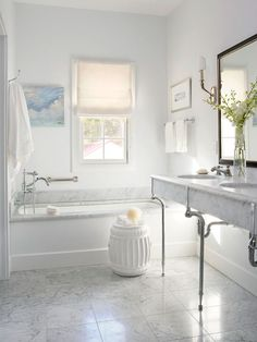 Simply Elegant  Soft white walls and dreamy Carrara marble accents fuse in this master bath to create a relaxing and restful retreat. Located beneath the modest bathroom's only window, the deep soaking tub becomes a focal point in the space. Sunlight filtering in above the tub brings out the shine of chrome finishes and gives the room a luminous glow.