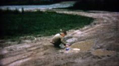 1962: Boy playing with toy boats in sad muddy driveway puddle. http://www.pond5.com/stock-footage/60000685?ref=StockFilm keywords:1962, Boy, playing, toy, boats, sad, muddy, driveway, puddle, 1960s, 8mm, film, old, home movie, vintage, retro, rare, unique, archival, Americana, documentary, editorial, history, classic, Son, child, front yard, home, rural, improvise, outside, rainy, weather, occupied, imagination, pretending, sailing, make do, fun, enjoyment, content, play, alone, friendless…