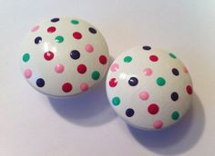 Hand Painted dresser knobs with pink, green, and purple polka dots on a white drawer knob  Find them at The Little Nursery for $4.50 each