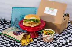 """Cuban Sandwiches: Catering With a Twist in Austin, Texas, serves boxed """"Cuban Sammies."""" Served with a side of arugula-corn-tomato salad, the sandwiches are filled with roasted pork tenderloin, honey ham, mustard, pickles, and onions and served on a sweet roll."""