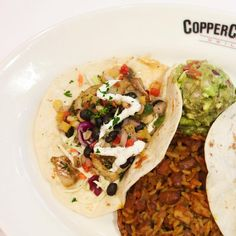Fish Tacos! Cabbage, sour cream and campfire sauce top two delicious tacos with Ranch beans, rice, and housemade guacamole on the side. #eeeeeats #coppercanyongrill #foodie #foodstagram #gaithersburg #silverspring