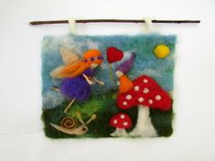 "Needle Felted Picture waldorf inspires for Nursery decor. This Lovely tapestry is made with wool,with needle felted technique On this picture there is sweet little purple fairy flying next to gnome that sitting on mushroom. The Picture/tapestry attach to wood stick for hand it on the wall. This Picture is a great decoration for children room bring harmony and happiness. Average Diameter:10*8.5""(25*21cm) I made it with LOVE AND CARE."