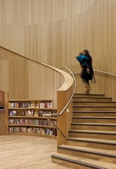 Thin, vertical wood slats pull the eye up even more in a tall space. Canada Water Library / CZWG Architects