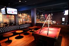 A bar-gaming paradise with 100 beers, potato chip nachos, and pinup girls