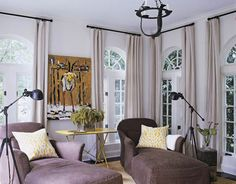Kay Douglass - House Beautiful:  In the sunroom, stone-brown slipcovered chaises are backlit by rows of windows dressed in Belgian linen. A bright yellow metal antique table provides a handy place for a glass of wine or cup of coffee.