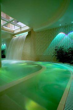 swimming pool indoors w/ waterfall & green lighting