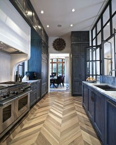 stained wood cabinets with white counters and tile floor   herringbone wood floor Kitchen Transitional with chevron flooring ...