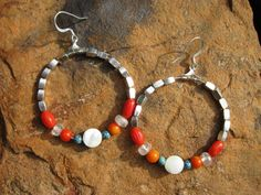 Beads of orange coral, turquoise, mother of pearl, and vintage crystals circle together in a refreshing combination. Threaded with silver plated