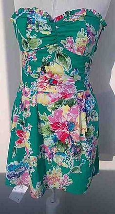 This is a short,medium,sleeveless,green dress.The dress has flower print,the dress has pleats,the dress has one resorte to on the waist