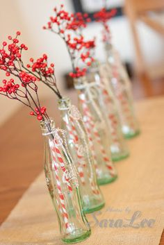 antique glass bottles + pretty red party straws + holly stuck inside straws + turquoise and red baker's twine tied around top of bottles
