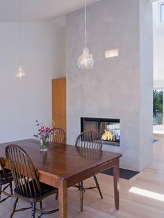 This striking two-way fireplace acts as a room divider, and the cool gray concrete creates a modern backdrop. Concrete may be strong and smooth, but it requires a sealant to make it water-resistant. Design by John Lum Architecture Stucco Fireplace, Two Sided Fireplace, Fireplace Tile Surround, Concrete Fireplace, Home Fireplace, Fireplace Remodel, Fireplace Surrounds, Fireplace Design, Double Fireplace