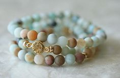 Amazonite, in pale green, milky blues, creamy yellows and rusty brown create a striking combination of colors for a fabulous set of stacking bracelets. The amazonite stretch bracelet is adorned with 14k gold filled rondelles and faceted rounds. The bracelet set is completed with and ever sparkeling gold druzy connector. All Amazonite are natural 6 mm beads. All you need this summer!  Set includes all three bracelets. Will fit 6 inch wrists loosely and will be more sung on 7 1/4 wrists.  ...
