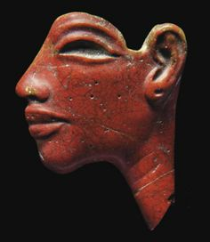 AN EGYPTIAN OPAQUE RED GLASS FACE INLAY OF AKHENATEN NEW KINGDOM, DYNASTY XVIII, CIRCA 1353-1336 B.C. With sensuous lips, recessed eye and eyebrow, pierced earlobe, faint traces of two 'vanity wrinkles' on the neck 1 5/8 in. (4.2 cm.) high