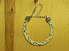 Very nicy bracelet, full of color with white background. Handmade jawelery with feather tag. Perfect for a gift! Enjoy!