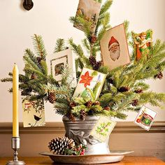This Christmas card display mixes classic Christmas decorations with vintage Christmas cards, and it's oh-so-simple. To create this display, place evergreen branches with pinecones still intact in a metallic pot — you can use fresh ones from the Christmas tree or timeless faux branches from a craft store. If the Christmas branches don't have pinecones, use floral wire to attach them for an holiday flourish. Arrange the holiday cards within the branches to finish off this Christmas card…