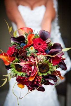 A clutch bouquet of burgundy antique hydrangeas, burgundy calla lilies, mango calla lilies, orange sunflowers, burgundy dahlias, blue thistles, seeded eucalyptus, burgundy ranunculus, burgundy cymbidium orchids, and red hypericum berries wrapped in ivory ribbon with the stems showing