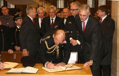 Prince Philip, Duke of Edinburgh signs the Gilden Book at the Townhall on November 11, 2013 in Ypres, Belgium.