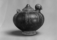 Lime Pot with Chicken Head and Tail Period: Angkor period Date: late 11th century Culture: Cambodia Medium: Stoneware (Khmer ware) Dimensions: H. 3 3/8 in. (8.5 cm); Diam. 3 1/2 in. (8.9 cm) Classification: Ceramics Credit Line: Gift of Mr. and Mrs. Uzi Zucker, 1984 Accession Number: 1984.498.1a, b