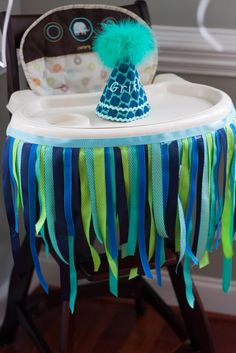 Decorated high chair with ribbon and custom birthday party hat - fun for a 1st birthday party cake smash!