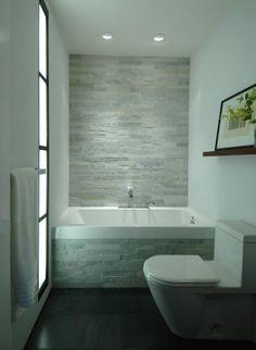 Een donkere vloer in combinatie met lichte stenen creëren een natuurlijke sfeer in deze badkamer.
