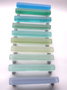 Hand carved glass is tumbled to a soft beach glass finish. It is then mounted on a nickel base. These are 4