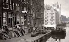 1916 Huizen met stoepen en trapjes aan de voorkant zodat de mensen even buiten konden zitten. Beddengoed ligt op de vensterbank, op de kade liggen houten vaten en verderop aan het water zijn pakhuizen te zien.