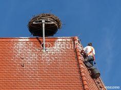 Dachdecker auf einem Kirchendach mit Storchenrad und Storchennest in Markt Burgheim