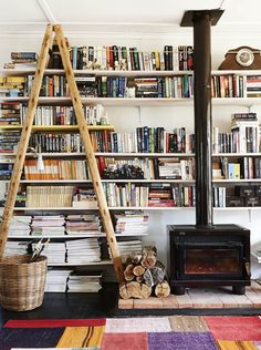 Great, simple white bookshelves behind a wood stove. The Design Files