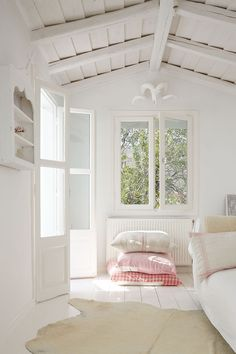 The+meditation+room+is+simply+furnished+with+a+white+daybed.+Pink+cushions+give+an+accent+of+colour.