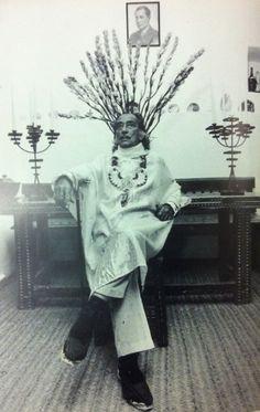 Dali posing in front of his photograph of Josè Antonio Primo de Revera, founder of Falange Espanola, the Spanish Facist part, Port Lligat