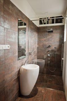 Salle de bain avec sa colonne de douche encastrée et vasque totem en céramique blanche adjacent aux murs en dalle cuivre