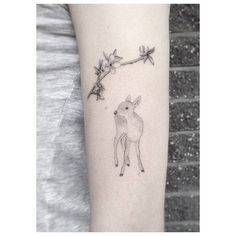 Fine line cherry blossom branch and fawn tattoo on the left upper arm.